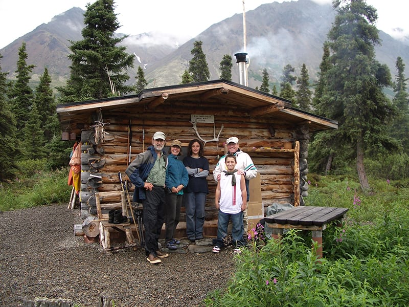 Family posing together outside Twin Lakes cabin
