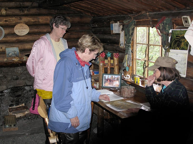 3 women explore inside of Twin Lakes cabin.